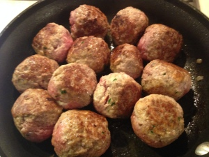 Homemade meatballs browning in the pan